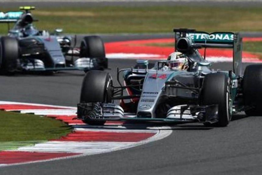 Mercedes AMG Petronas F1 Team's British driver Lewis Hamilton (right) and Mercedes AMG Petronas F1 Team's German driver Nico Rosberg drive during the British Formula One Grand Prix at the Silverstone circuit in Silverstone on July 5, 2015.