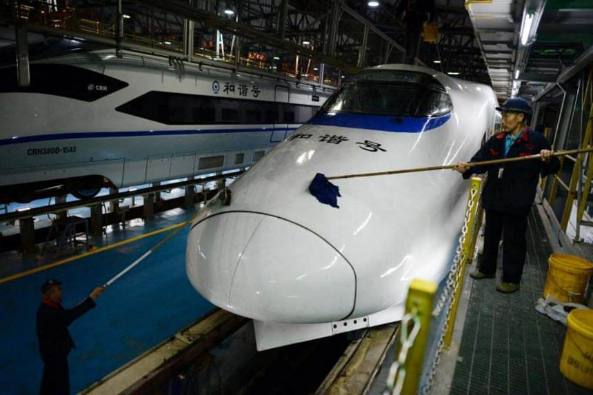 A photo taken on May 5, 2017 shows workers cleaning a high-speed train at a maintenance and cleaning center for China's high speed rail network, in Chongqing, southwest China.