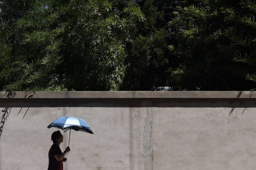 pedestrian shielding herself from the sun in Beijing, on July 10, 2017.