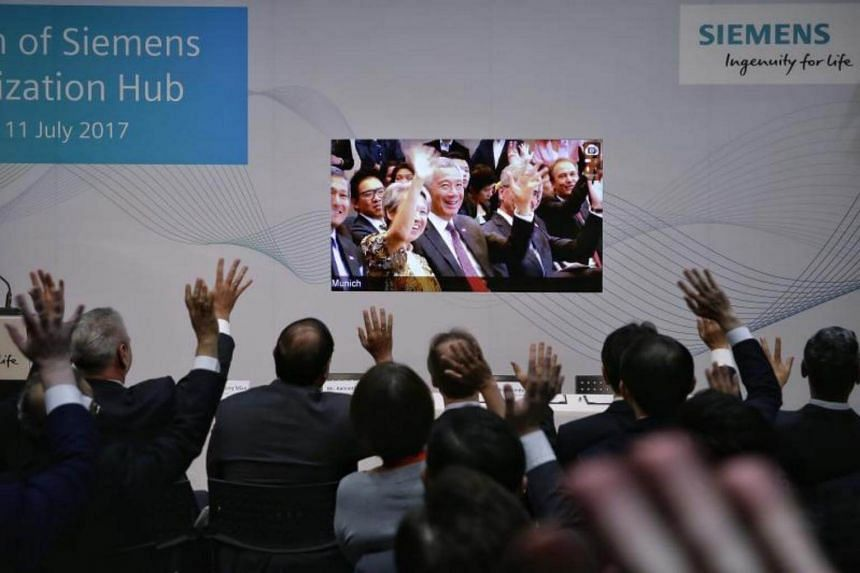 Prime Minister Lee Hsien Loong and wife Ho Ching waving over a live video feed from Munich to Minister for Trade and Industry (Industry) S Iswaran and Siemens representatives in Singapore on July 11, 2017.