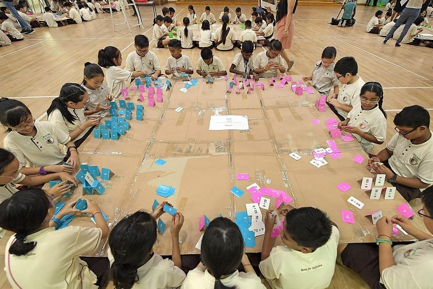 Primary 4 pupils of Boon Lay Garden Primary School building card houses on a large cardboard canvas resting on the laps of their peers. The set-up encouraged cooperation as any movement could cause the canvas to shake and make the houses fall. It was
