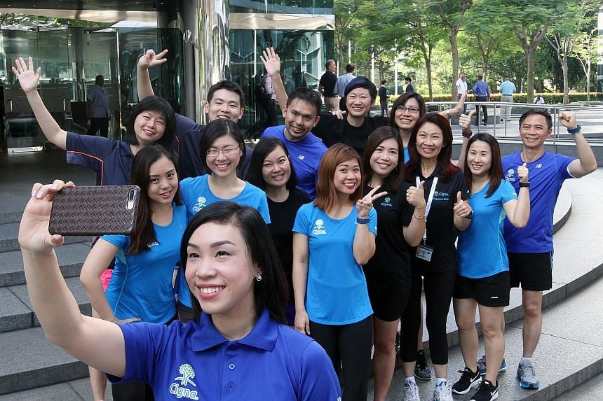 Ms Lena Tsia (third from right), chief executive officer of the Singapore branch of Cigna, which focuses on health insurance, with some of the firm's employees who will be taking part in Sunday's ST Run.