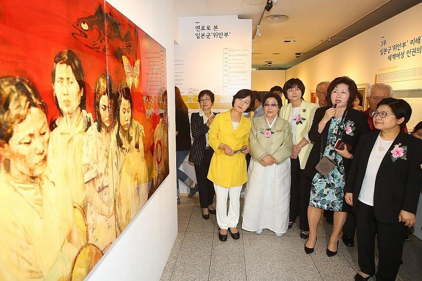 Gender Equality Minister Chung Hyun Back (right) and survivor Lee Yong Soo (third from left) viewing an exhibit on comfort women at the National Museum of Korean Contemporary History in Seoul yesterday. A screen grab from rare footage unearthed last