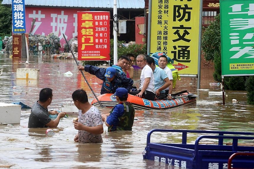 People being evacuated from a flooded area in Loudi city, Hunan province, on July 1. Days of downpours have brought floods to vast areas in southern China.