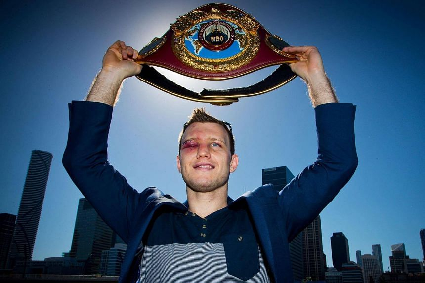 Newly crowned World Boxing Organization (WBO) welterweight champion Jeff Horn posing for photographs with his belt after a press conference in Brisbane.