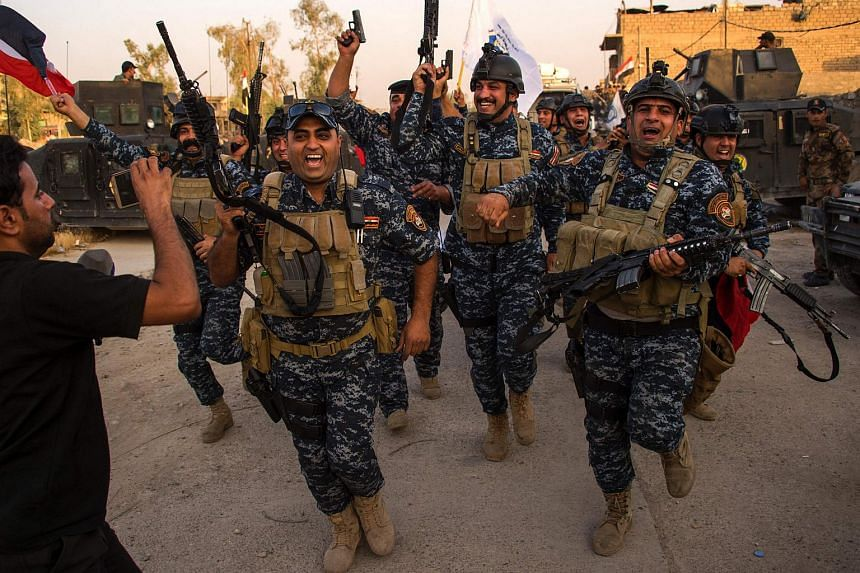 Members of the Iraqi forces celebrate in the Old City of Mosul on July 10, 2017.
