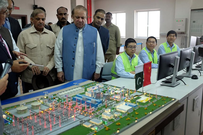 Pakistani Prime Minister Nawaz Sharif listens as experts explain a process of the Haveli Bahadur Shah LNG power plant during the inauguration in Jhang, Pakistan, on July 7, 2017.