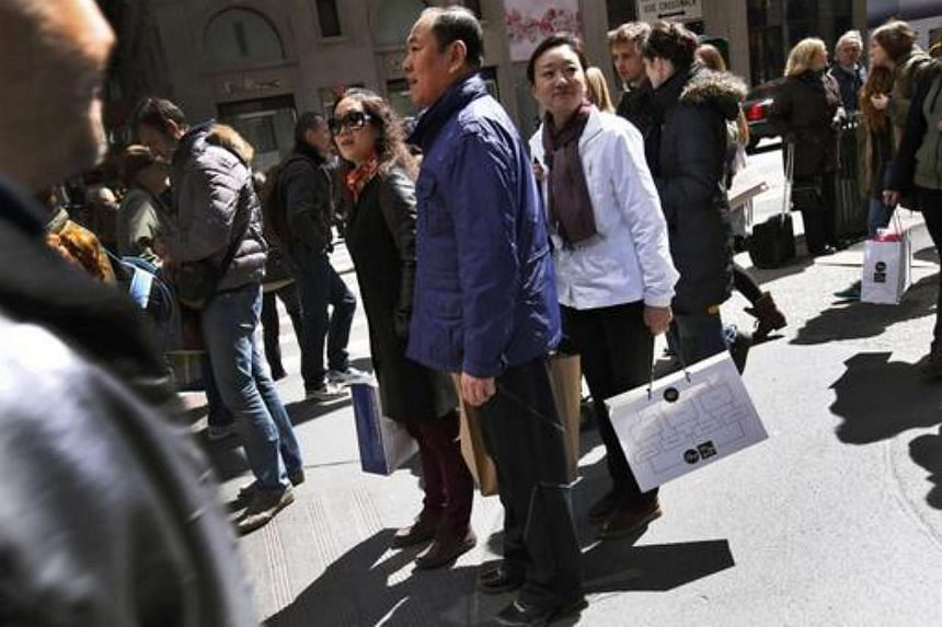 Chinese shoppers standing with shopping bags on a sidewalk along 5th Avenue in New York City, on April 4, 2013.