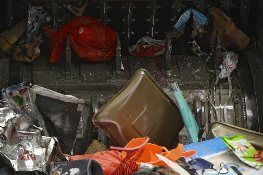 Bags of unsorted rubbish are placed in a machine, which rips the bags open and drops the items within onto moving conveyor belts, at SembWaste's Materials Recovery Facility in Tuas.