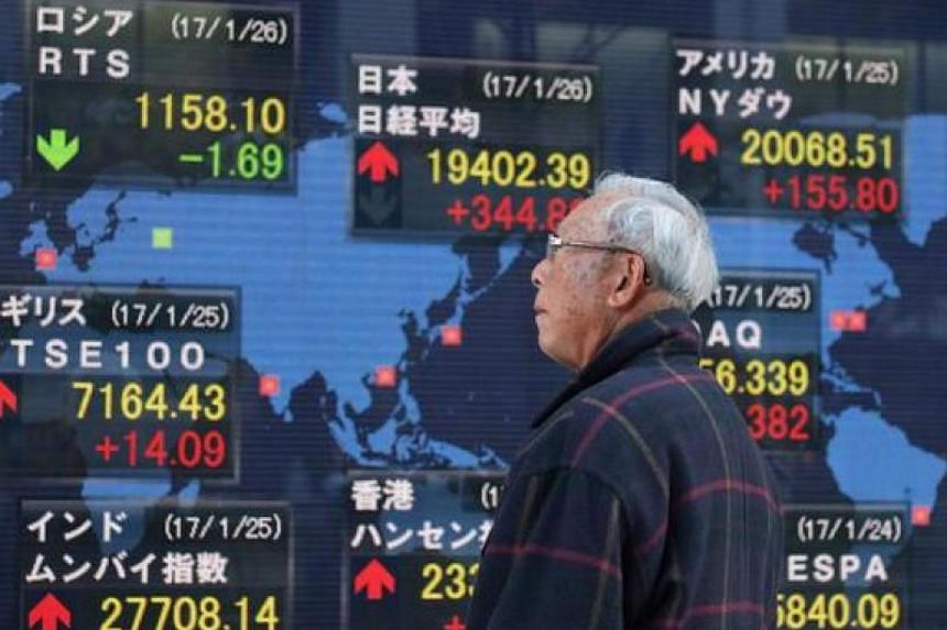 A pedestrian looks at an electric quotation board flashing stock prices on the Nikkei key index of the Tokyo Stock Exchange.