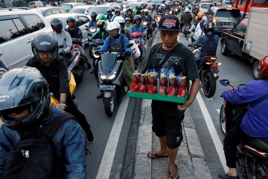 A street vendor selling beverages to motorists during rush-hour traffic in Jakarta on June 14, 2017. Urban issues in Indonesia's capital including regular traffic congestion on the main thoroughfares and highways to the suburbs.