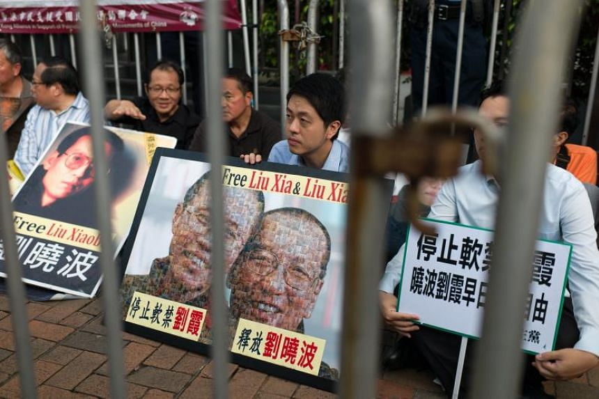 Activists from the Hong Kong Alliance in Support of Patriotic Democratic Movements of China hold photographs of Chinese dissident and Nobel Peace Prize laureate Liu Xiaobo during a rally outside the China Liaison Office in Hong Kong on July 10. The a