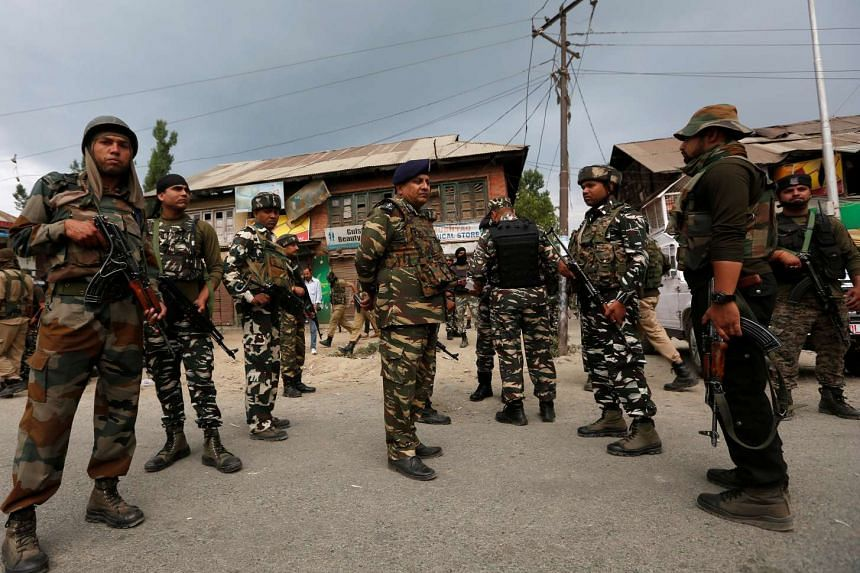Indian security force personnel stand at the site of a gunbattle between Indian police and militants on Monday in which seven Hindu pilgrims were killed, in Boateng village in south Kashmir's Anantnag district on July 11, 2017.