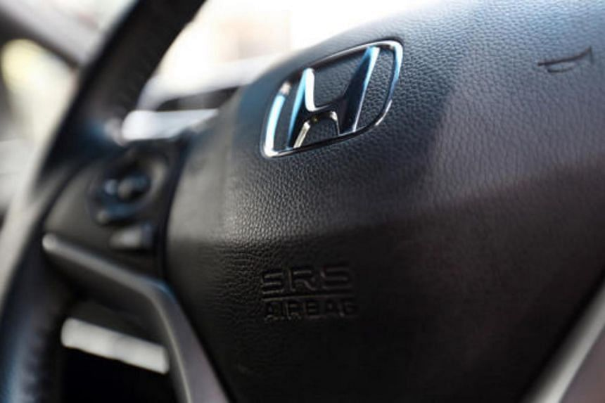A Honda Motor badge and airbag unit for the drivers seat are seen on the steering wheel of a Fit Hybrid vehicle in Tokyo, Japan.