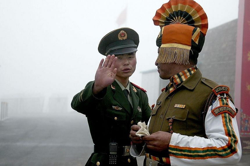 A 2008 file photo showing a Chinese soldier and an Indian soldier at the Nathu La border crossing between India and China. The two sides have a festering row along several areas of their 4,000km-long border.