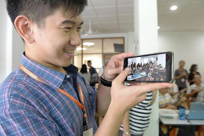 St Francis Methodist School student Kelvin Russell, 17, taking a video of the elderly jamming during their weekly ukulele session yesterday at the Charis Activity Centre for Elders. As part of the Impacting Lives Challenge 2017, the Methodist Welfare