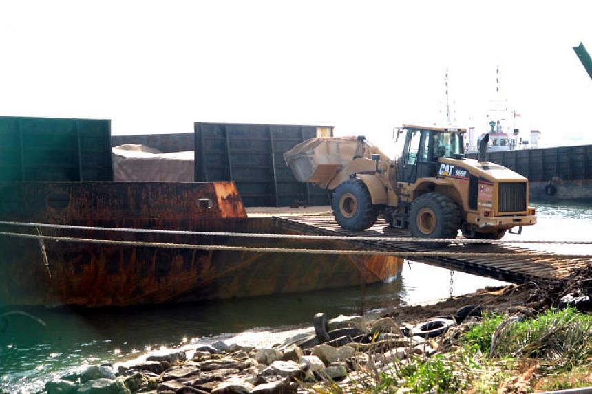A bulldozer unloads sand for the construction industry from a barge at Tuas South Avenue 3 Agregate Terminal.