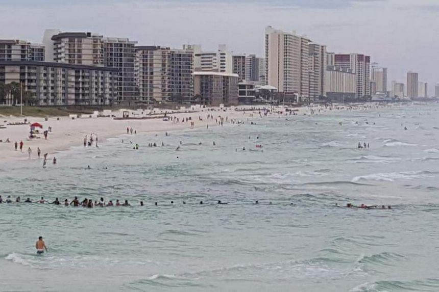 Dozens of beachgoers at Panama City Beach form a human chain to rescue nine stranded swimmers swept away by a strong riptide on Saturday (July 8).