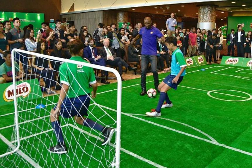 Fromer Barcelona defender Eric Abidal (in purple) participating in a kickabout at the Singapore Sports Hub's OCBC Lounge on 19 January.