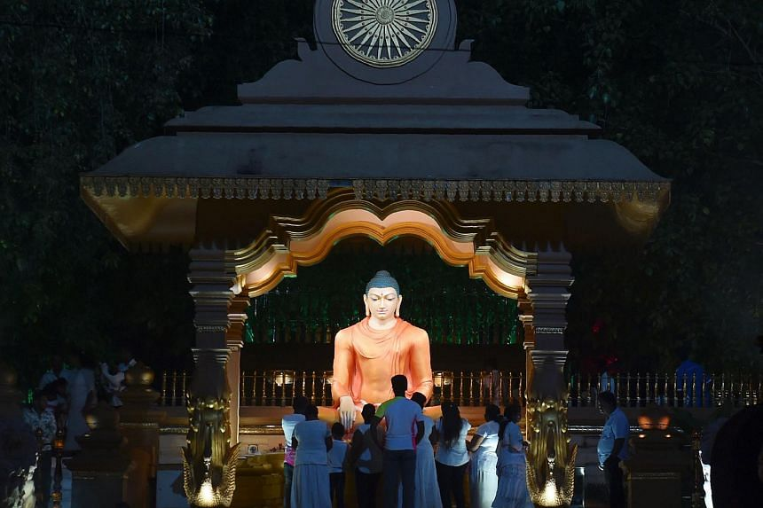 Sri Lankan Buddhists devotee pray during Poya, a full moon religious festival in a temple in the Colombo suburb of Kaduwela on July 8, 2017.
