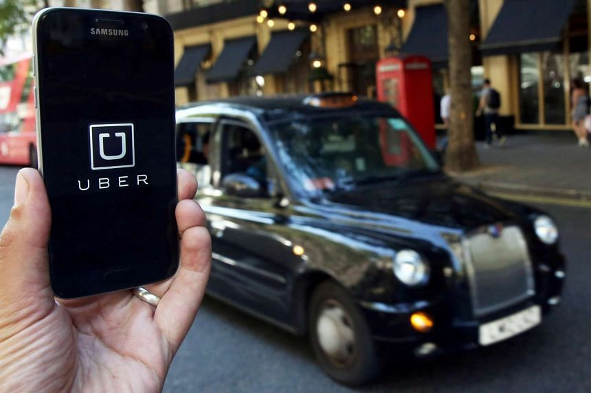 A photo illustration shows the Uber app logo displayed on a mobile telephone, as it is held up for a posed photograph in central London.