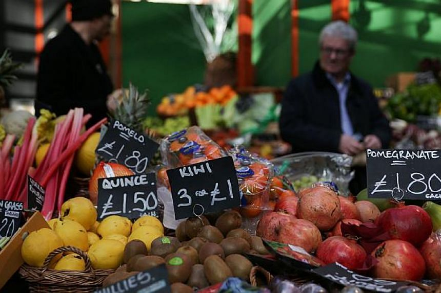 Signs displaying the price in pounds sterling of fruit and vegetables at a food stall in a street market in southeast London.