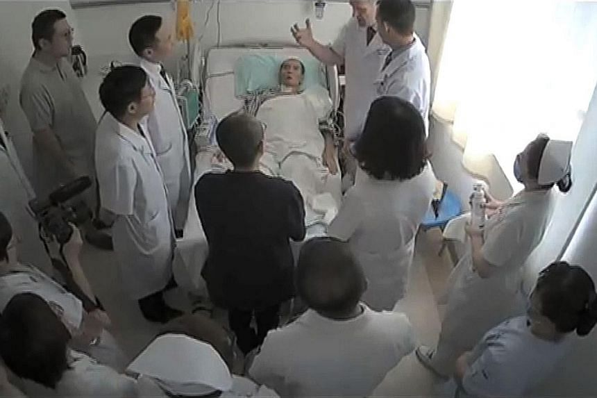 A video (left) leaked earlier this week showing Mr Liu Xiaobo (above) surrounded by doctors and his wife Liu Xia (in dark outfit). Mr Liu was admitted to the hospital last month for late-stage liver cancer.