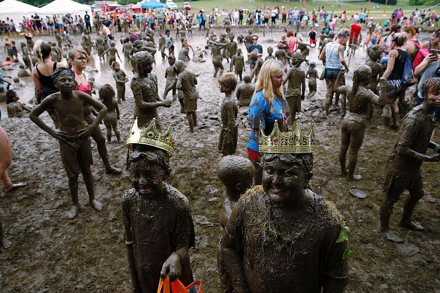 Mackenna Kofahl (left), 12, and Brian Wilson 10, being crowned Mud Day Queen and King as part of the annual Mud Day at Nankin Mills Park in the American state of Michigan on Tuesday. It takes more than 181 tonnes of top soil and 75,700 litres of wate