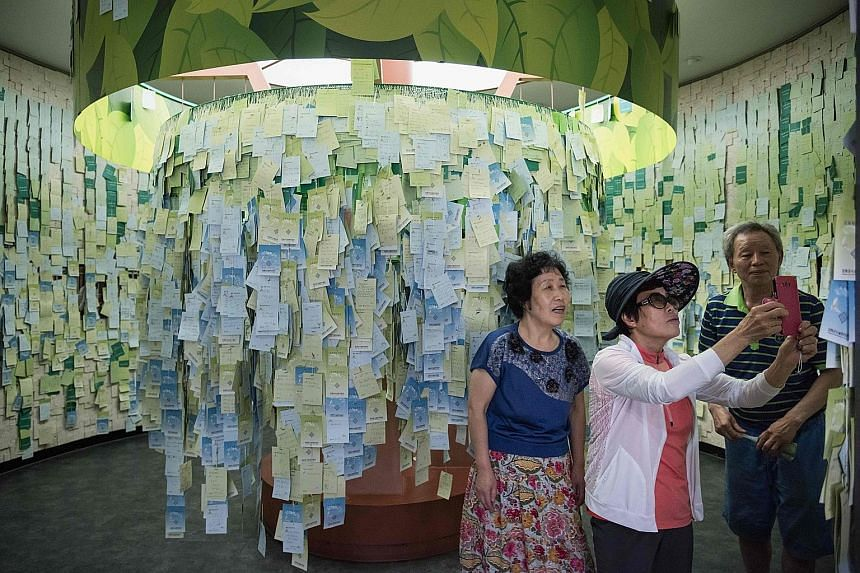 Visitors taking snapshots of messages calling for reunification at an observatory near the Demilitarised Zone (DMZ) separating the two Koreas on the island of Ganghwa, west of Seoul, on Tuesday. In the six months to June, 593 Northerners escaping pov