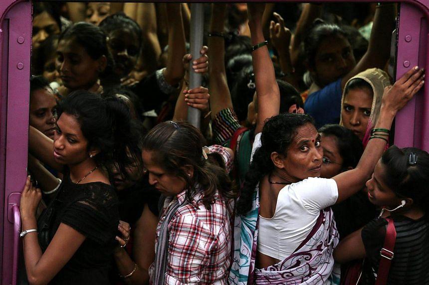 Women board a local train in Mumbai, India.