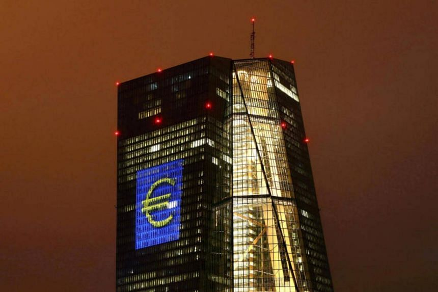 A giant euro sign lights up the headquarters of the European Central Bank (ECB) in Frankfurt, Germany on March 12, 2016.
