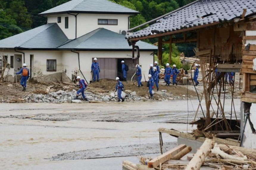 Police personnel conduct a search and recovery operation for missing victims in a flood-affected area in Asakura city, Fukuoka prefecture on July 11, 2017.