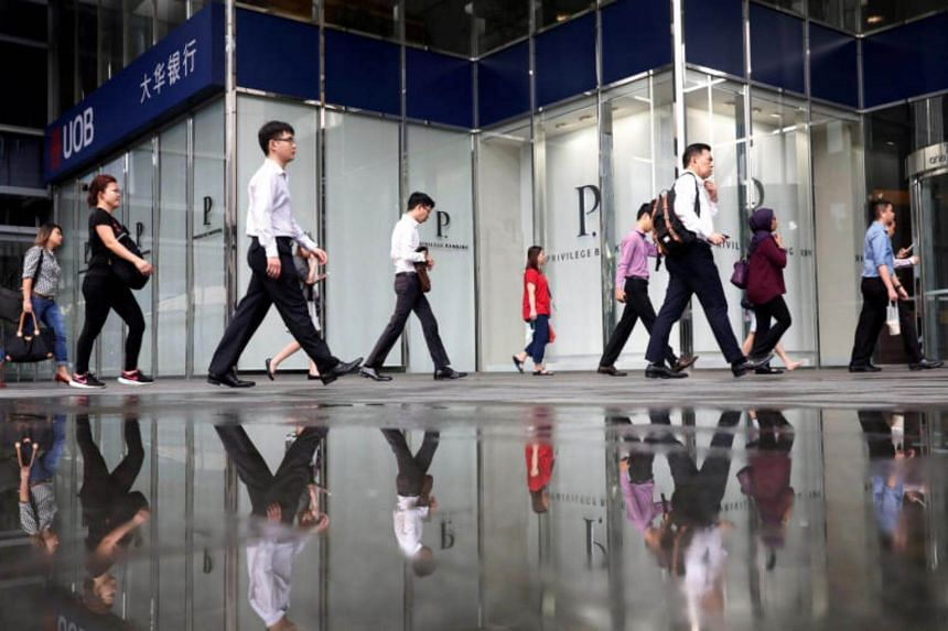 Office workers pass a UOB bank branch in Singapore's central business district on April 27, 2017.