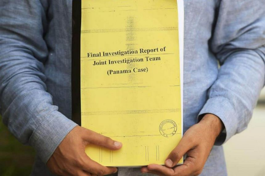 A Pakistani journalist holds a copy of a corruption report in Islamabad on July 12, 2017.