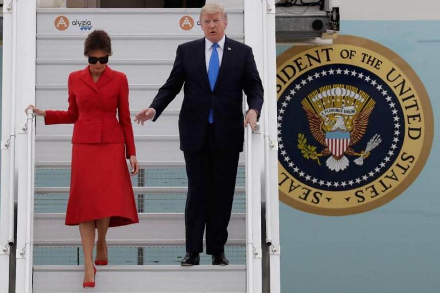 US President Donald Trump waves as he disembarks form Air Force One with First Lady Melania on July 13, 2017 at Paris' Orly airport.