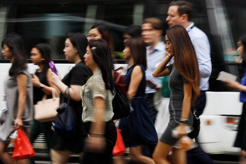 Office workers cross a street in Singapore's central business district on April 27.