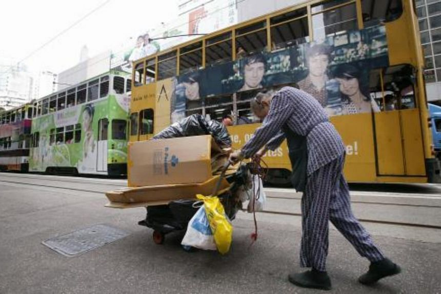 An elderly woman pushes a trolley load of cardboard for recycling through a market in the Wanchai district of Hong Kong.