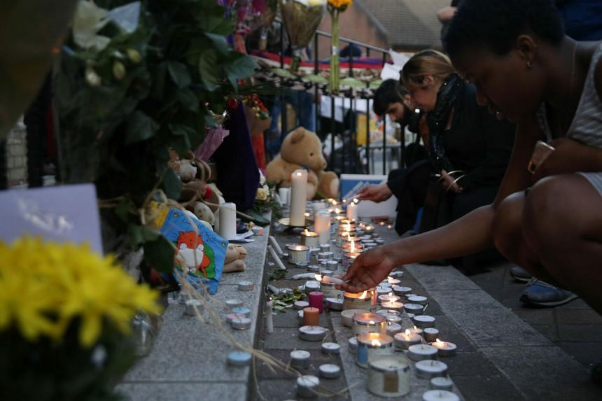 People light candles during a vigil outside Notting Hill Methodist Church following the blaze at Grenfell Tower, on June 15, 2017.