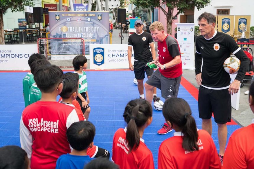 FC Bayern Munich youth coach Thomas Doellner (in red) conducting a public clinic at the Fountain Square in Clarke Quay on June 11, 2017.