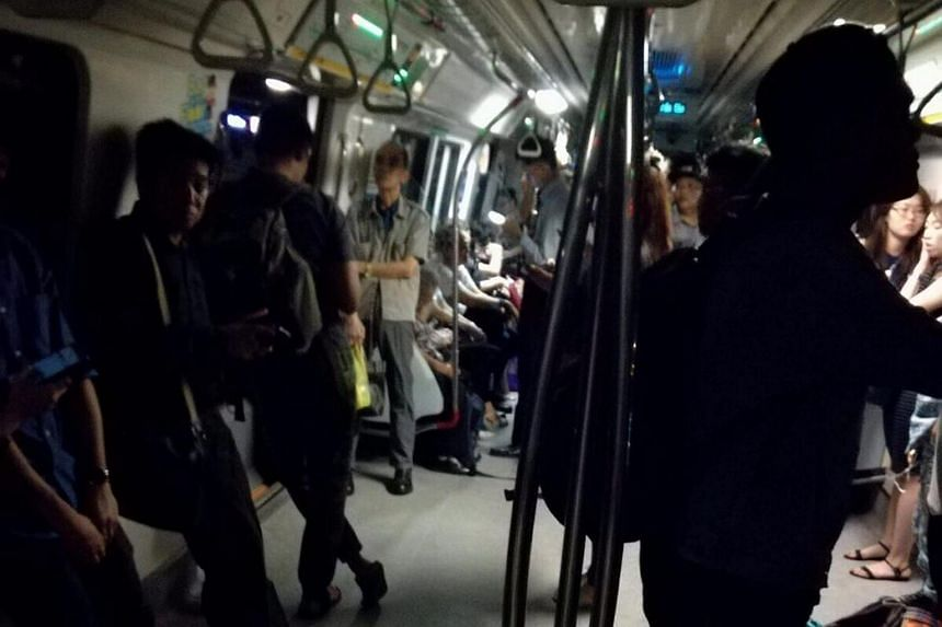 Passengers standing in semi-darkness in an MRT train after a power blackout affected train services on parts of the train network on July 12, 2017.