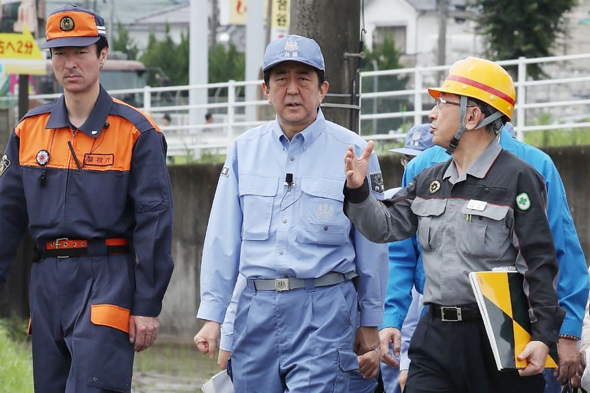 Japanese Prime Minister Shinzo Abe (centre) inspecting a flood-affected area in Hita, Oita prefecture, yesterday. The death toll from heavy rain and flooding in Japan's south has risen to 25. Mr Abe has promised help to rebuild the devastated region.
