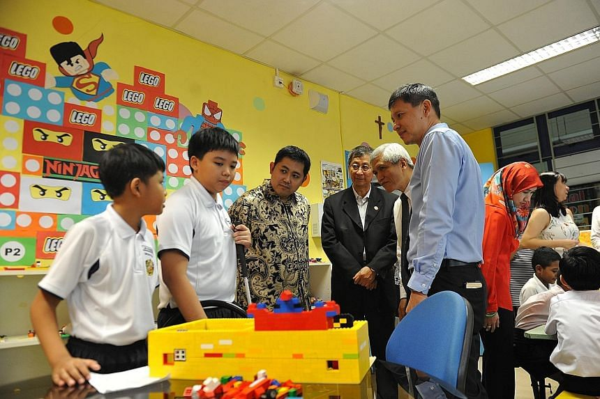 Primary 6 pupils (from left) Mohammad Syahmi Iman Mohammad Shahril and Joshua Babol showing off their creations, which included a lightsaber, in Montfort Junior School's Lego Room and all-new Tinker Room to Prince Abdul Qawi of Brunei (in batik shirt
