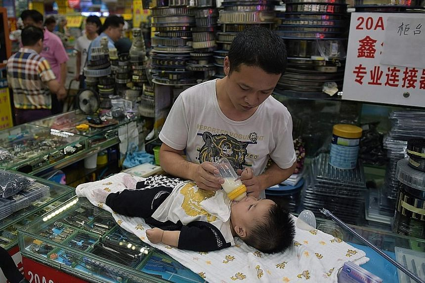 A Chinese man feeding his baby at a Shenzhen mall. For decades, couples in urban China could have only one child, but the country, which is trying to boost its shrinking workforce, ended that policy in 2015.