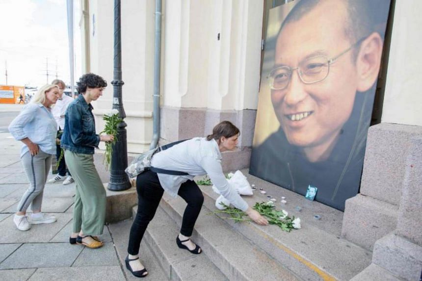 People lay flowers and light candles outside the Nobel´s Peace center in Oslo, Norway in front of a photo of Nobel peace laureate Liu Xiaobo who died on July 13, 2017.
