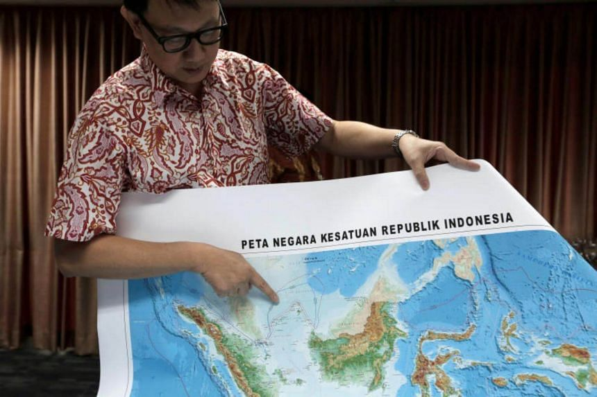 Indonesia's Deputy Minister for Maritime Affairs points to the location of North Natuna Sea on the new map of Indonesia during talks to reporters in Jakarta, Indonesia on July 14, 2017.