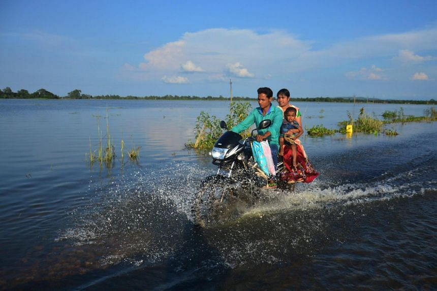 An Indian family travels along a flooded road on a motorbike in the district of Kamrup in Assam on July 13, 2017.