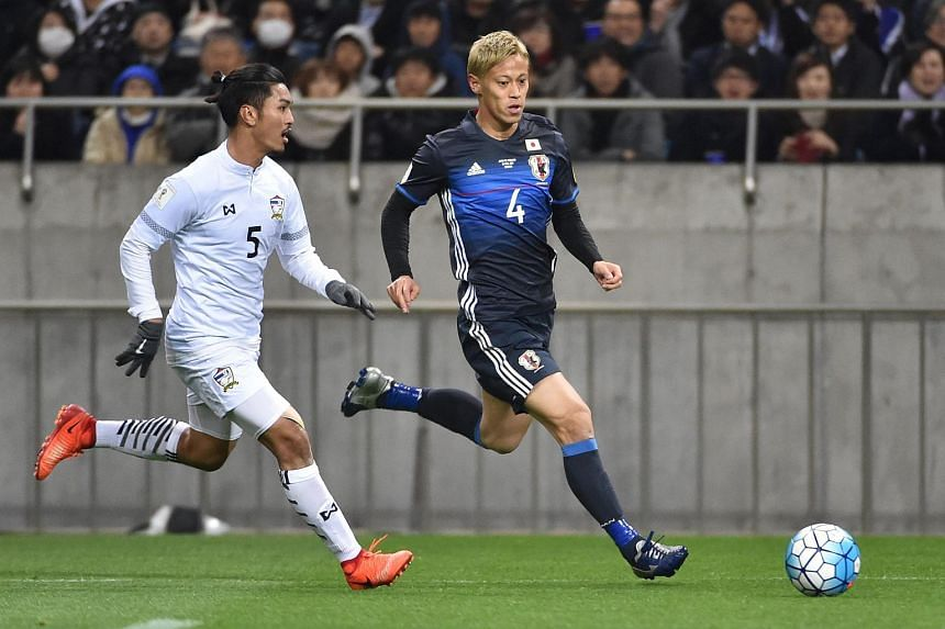 This file photo taken on March 28, 2017 shows Japan's forward Keisuke Honda (right) and Thailand's defender Adison Promrak (left) during group B World Cup 2018 qualifying football match between Japan and Thailand in Saitama.