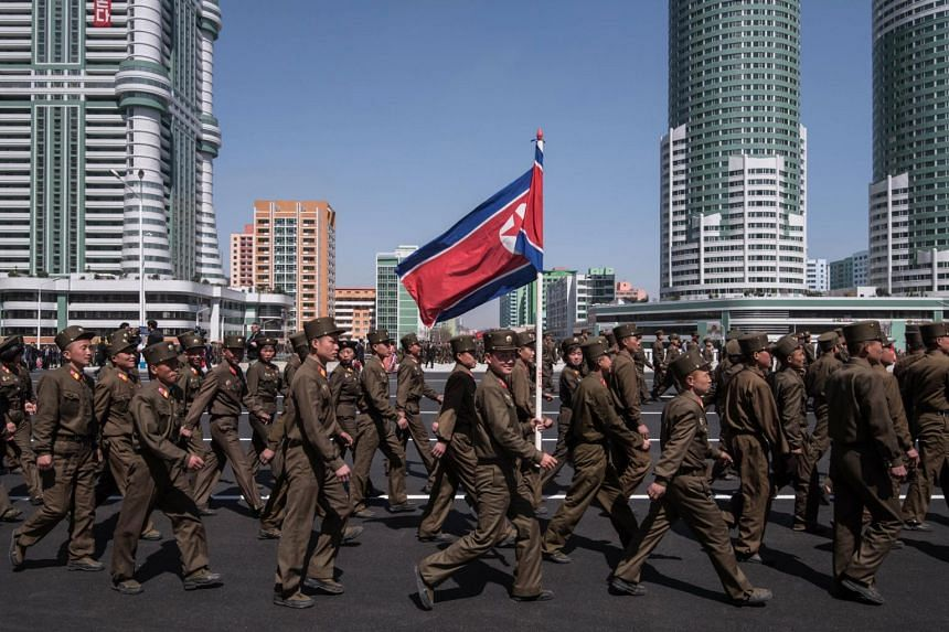 Korean People's Army (KPA) soldiers walk along a road in the Ryomyong Street housing development following its opening ceremony in Pyongyang on April 13, 2017.