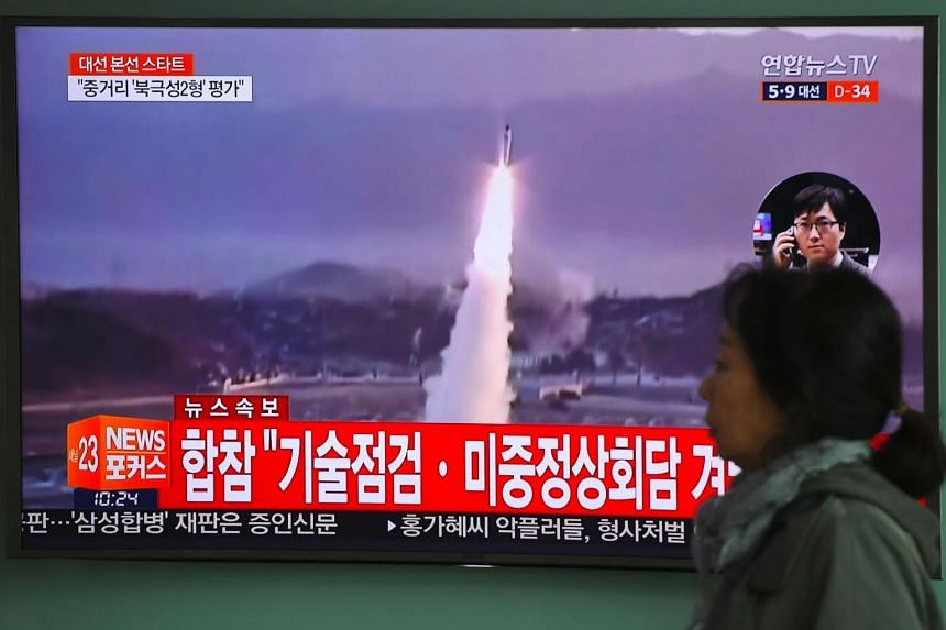 A woman walks past a television screen showing file footage of a North Korean missile launch.