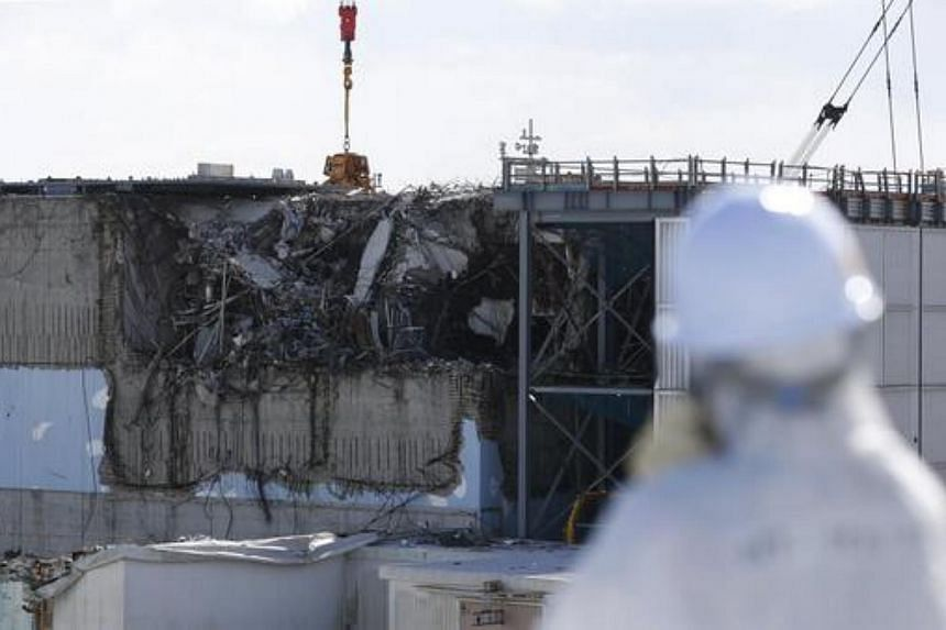 A member of the media, in a protective suit and mask, viewing the No. 3 reactor at Tepco's tsunami-crippled Fukushima Daiichi nuclear power plant.